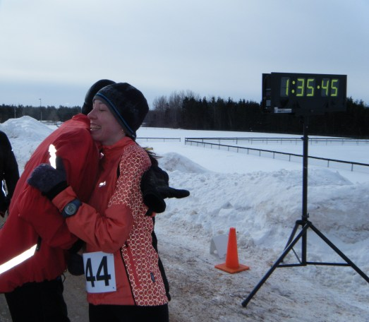 Racers hug at a half marathon finish line