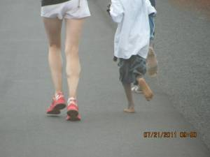 A Canadian girl runs with a barefoot African Child